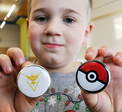 John P. Cleary |  The Herald Bulletin<br /> Collin Forster, 7, shows off the two buttons he made during the Holiday Boredom Busters event at the Anderson Public Library Wednesday afternoon.