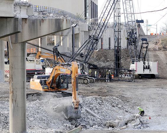 Don Knight    The Herald Bulletin<br /> An excavator picks up a piece of the Eisenhower bridge to carry it away as the westbound span is being demolished on Thursday.