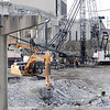 Don Knight |  The Herald Bulletin<br /> An excavator picks up a piece of the Eisenhower bridge to carry it away as the westbound span is being demolished on Thursday.
