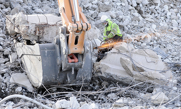 Don Knight |  The Herald Bulletin<br /> A worker cuts through rebar as a beam from the Eisenhower bridge is broken up during demolition on Thursday.