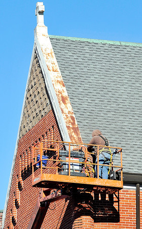John P. Cleary |  The Herald Bulletin<br /> On a cold, windy day this worker for Wells Masonry works high on a lift to reach the bricks on the west side of St. Mary's Catholic Church while doing tuck pointing work on the structure.