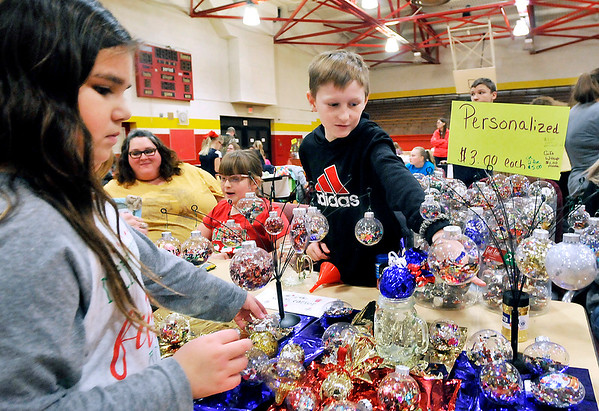 John P. Cleary |  The Herald Bulletin<br /> Aaron Carter, 10, points out some items to Adrienne Salazar, 8, as she looks over the personalized ornaments Aaron was selling at the Alexandria Intermediate School Kidpreneur Holiday Market this week.