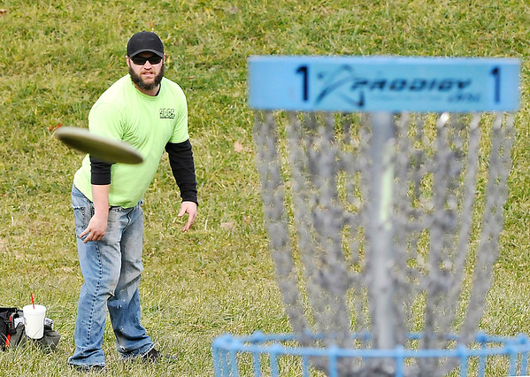 John P. Cleary |  The Herald Bulletin<br /> Logan Carpenter, of Anderson, watches his shot fly toward the basket as  he plays disc golf at the new Sanders Memorial course in Edgewater Park Monday afternoon. Carpenter and his friends were taking advantage of the warm weather to get another round in before the weather turns cold.