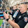 John P. Cleary |  The Herald Bulletin<br /> Anderson FOP provided Christmas for 80 children during their annual Shop With A Cop program at Meijer's. Anderson Police officer CJ Christian shows Carson Edmonds, 2, a train as Carson tries to decide which toy to chose.