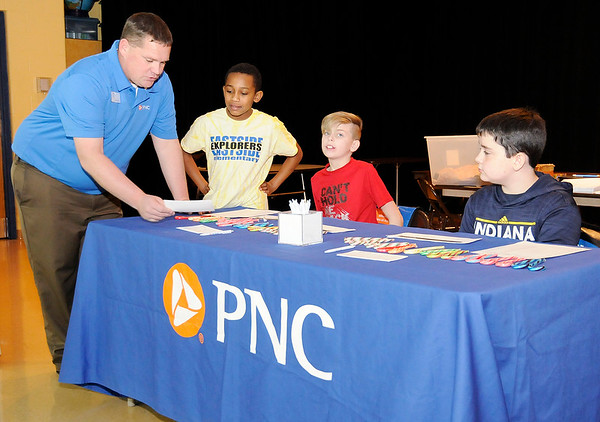 Don Knight |  The Herald Bulletin<br /> Chris Spolyar from PNC goes over details with his 5th grade tellers for the day before the start of the lunch hour. Students from left, are Brycen Carter Jackson Richardson and Nick Kestner.