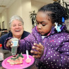 John P. Cleary |  The Herald Bulletin<br /> Shawnnee Perry, 4, decorates her cookie at the Soroptimists' Celebrity Cookie Walk Friday afternoon with the assistance of Soroptimist member Julie Morse.