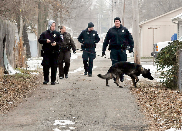 John P. Cleary | The Herald Bulletin<br /> Anderson Police K-9 unit with APD officers and Sheriff units search along the alley running between Broadway and Poplar Streets for evidence after the Key Bank at 2246 Broadway was robbed Monday afternoon.