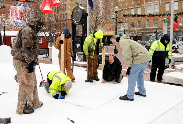 Don Knight | The Herald Bulletin<br /> City workers assemble a synthetic skating surface at Dickmann Town Center on Wednesday. The rink will be open every day until Jan. 15th except for Christmas Day and New Year's Day.