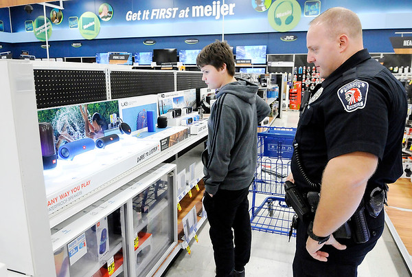 Don Knight   The Herald Bulletin<br /> APD officer Travis Thompson helps James Allmond, 14, pick out a blue tooth speaker during  the FOP's Cops & Kids Program at Meijer on Tuesday.