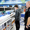 Don Knight | The Herald Bulletin<br /> APD officer Travis Thompson helps James Allmond, 14, pick out a blue tooth speaker during  the FOP's Cops & Kids Program at Meijer on Tuesday.