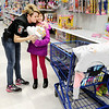 Don Knight | The Herald Bulletin<br /> APD's Heather McClain gets a hug from Sabrina Batana, 9, during FOP's  Cops & Kids Program at Meijer on Tuesday.