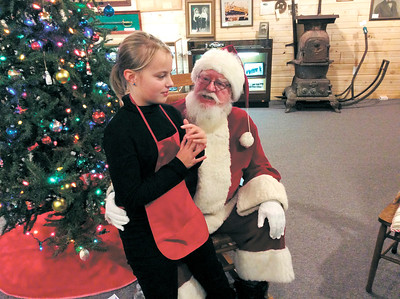 Lachlan Brown, 10, a fourth-grader at East Elementary School, visits with Santa on Sunday during the Pendleton Historical Society's Christmas open house.  Rebecca R. Bibbs   The Herald Bulletin