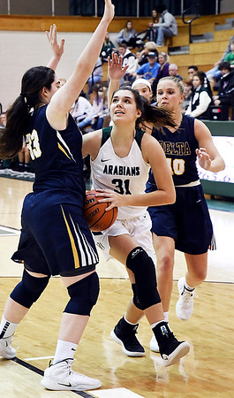 John P. Cleary   The Herald Bulletin<br /> Pendleton's Aubree Dwiggins splits Delta defenders as she drives to the basket for a shot.