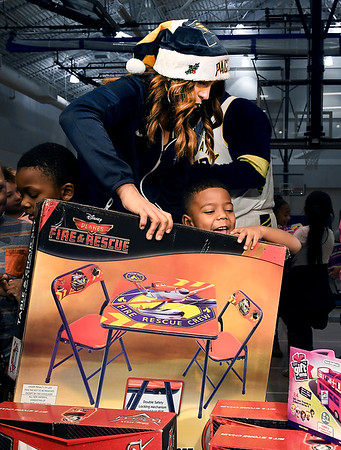 John P. Cleary | The Herald Bulletin Anderson Elementary kindergartener Ra'Monte Brown is all smiles as Pacemate Brooke helps him carry his new toy he received from the Jakks Pacific - Pacers toy giveaway held at the school Thursday.