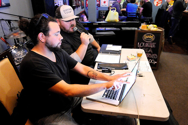 Don Knight | The Herald Bulletin From left, Justin Alley and Kyle Buck go over the halftime scores during Top Live Trivia at Kettle Top Brewhouse on Tuesday.
