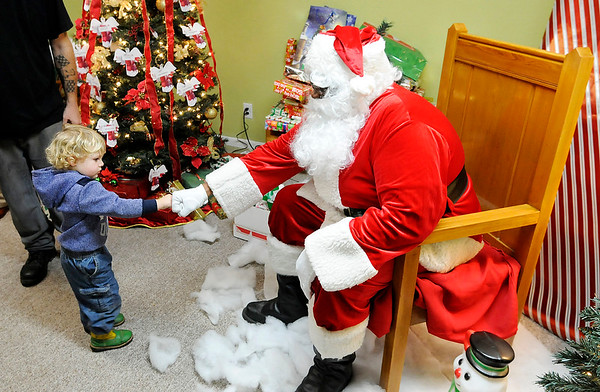 Don Knight | The Herald Bulletin Chevy Galbreath, 2, fist bumps Santa during Anderson Housing Authority's Christmas Party at Westvale Manor on Thursday. Housing Authority staff and board members decided to have the party for residents as a way to show their appreciation for them.