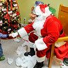 Don Knight | The Herald Bulletin<br /> Chevy Galbreath, 2, fist bumps Santa during Anderson Housing Authority's Christmas Party at Westvale Manor on Thursday. Housing Authority staff and board members decided to have the party for residents as a way to show their appreciation for them.