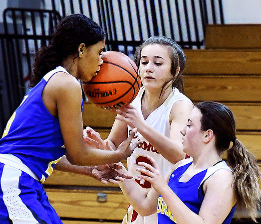 John P. Cleary   The Herald Bulletin<br /> Muncie Burris players Jasie Johnson and Jenna Lis with Liberty Christian's Irelynd Evans try to get a handle on this loose ball as Johnson gets a face-full of ball.