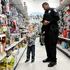 Don Knight | The Herald Bulletin<br /> APD's Joshua Owens keeps a total on his phone as he shops with Chance Lane, 6, during FOP's  Cops & Kids Program at Meijer on Tuesday.