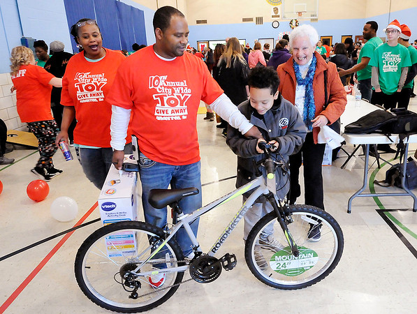 Don Knight | The Herald Bulletin<br /> Lindsay Brown gives Thomas Jackson, 10, a bike during the City Wide Toy Giveaway at the UAW on Saturday.