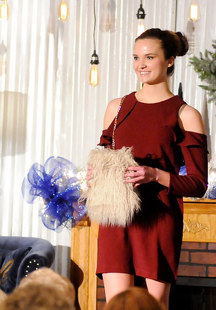 Don Knight   The Herald Bulletin<br /> Olivia Dunn models a cold shoulder dress and fuzzy purse during the Christmas Tea at Gaither Studios on Saturday.