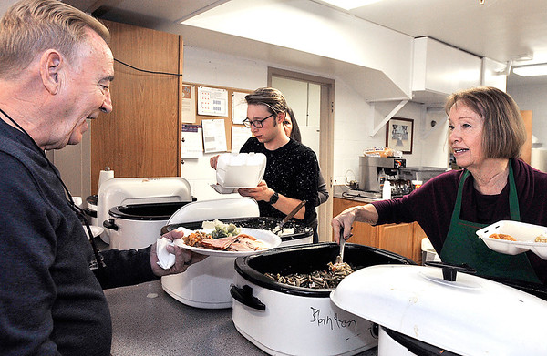 John P. Cleary   The Herald Bulletin<br /> Tim Patton gets a serving of green beans from Sylvia Clark during the annual St. Mary's Catholic Church Christmas day dinner in Alexandria.