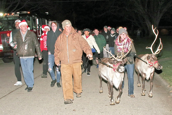 Tony Dare and Jordan Atwood lead a procession of Christmas Carolers with raindeer from Tenth Street School to the home of cancer-sricken Anderson Firefighter Brent Holland on Sunday evening.  (Mark Maynard photo)