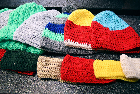 Some of the colorful hats and ear warmers crocheted by Malaki Huffer.