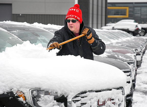 Nathan Renz had a busy Monday morning cleaning off the snow from vehicles after four inches of the white stuff fell overnight. Renz is a sales person at Myers Autoworld where there was plenty of inventory on the lot to clean off.