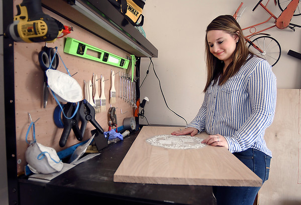 Hilary May, with her home decor product business, works in a small work shop in a corner of her garage to make the products she sells.