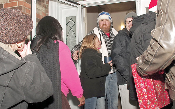 Brent Holland greets and thanks well-wishers after a large group of them sang Christmas carols outside his home on Sunday evening.  (Mark Maynard photo)