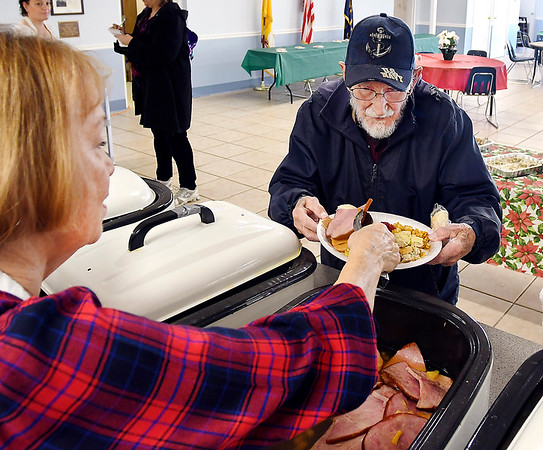 Sylvia Clark serves up ham for Gene Smith of Elwood Wednesday during the annual Christmas dinner put on by St. Mary's Catholic Church in Alexandria.