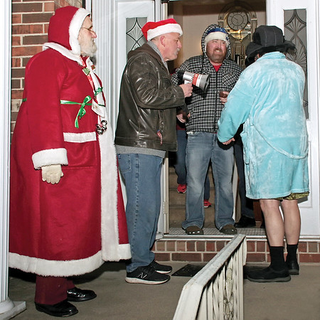 "Anderson Firefighter Brent Holland is greeted at his front door by Father Christmas (Baker), fellow firefighter Skip Ockoman and Cousin Eddie from ""Christmas Vacation""  (Anderson Fire Department Chaplain Tony Owen) accompanied by a throng of Carolers on Sunday evening.  (Mark Maynard photo)"