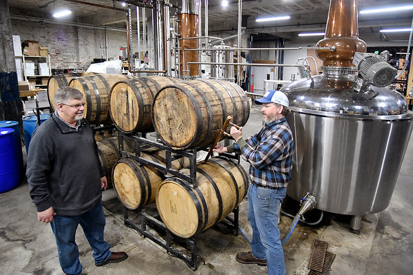 Jason and Jerrad Oakley check some of their barreled whiskey in their production area of their Oakley Brothers Distillery.