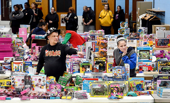 The Salvation Army and Marine Corp League held their annual Christmas toy giveaway Monday at the UAW Union Hall. Here Marine Corp League member Michael Cotton assists Hanna Garrett with picking out items as others wait their turn in the background. This was the biggest year for the Marine Corp League's Toy for Tots campaign.