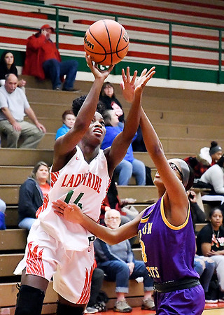 Anderson's Makyre Dixon goes up for a shot while working the baseline against Marion's Ashanti Cardine.