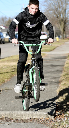 Tyler Summers, 12, jumps the curb as he rides his bike along Crystal Street in North Anderson enjoying the spring-like temperatures. Summers, from Muncie, was in town visiting relatives for the holidays.
