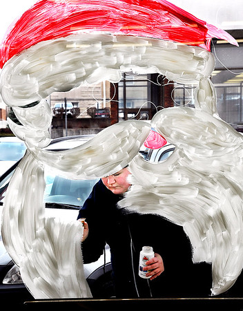 Shelby Murphy fills in Santa's beard as she and her father, Eric Murphy, paint the windows of T & J Tire at Ninth and Jackson Streets Tuesday afternoon in preparation for the City of Anderson's 2019 Christmas Celebration this Saturday.