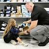 Anderson Police officer Travis Thompson helps Madison Munday, 9, pick out a new pair of shoes as they shop together at Meijer Tuesday morning during the annual Cops & Kids program.