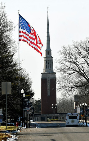As the late afternoon sun silhouettes Park Place Church of God's steeple, it highlights the giant America flag at Storage of America as Old Glory waves in the gentle breeze filling the sky with color along East  5th Street.