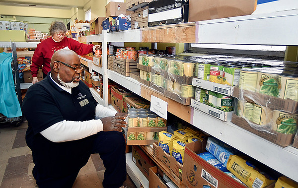 Volunteer Princess Johnson, background, and pantry assistant Curtis Mathis sort out these food items that have been donated for the Operation Love Ministries Christmas Wishes program Christmas food baskets.