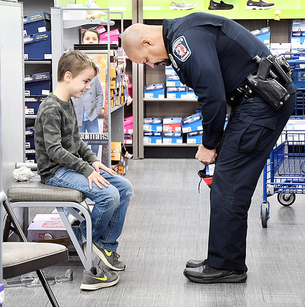 Landon House, 8, waits patiently as APD officer Dave Carroll unlaces the shoe he wants to try on as they shop together at Meijer during the annual Cops & Kids program held Tuesday.