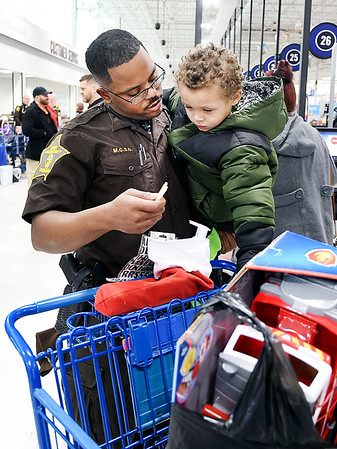 Madison County Sheriffs deputy Najee Reynolds offers a piece of candy to Nolland Fields, 3, as they say goodbye after their shopping together during the annual Cops & Kids program held Tuesday at Meijer.