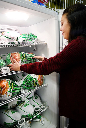 Operation Love Ministries pantry coordinator Lauren Simpson checks the frozen turkeys as they prepare for their Christmas Wishes program in which 300 families that have registered will receive a Christmas food basket that will include all the traditional trimmings and, depending on the family size, will include a turkey, ham or chicken.