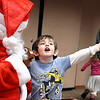 Four year-old Kaydyn Mires gets all excited as he tells Santa what he wants for Christmas during the Cookies with Mr. and Mrs. Claus event at the Anderson Public Library Monday afternoon. There was a special holiday-themed storytime with Mrs. Claus and a chance to visit with Santa himself along with each child receiving a free book to take home.