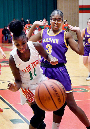 Anderson's Makyra Dixon and Marion's Ashanti Cardine lose control of the ball after fighting for possession.
