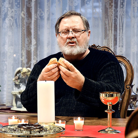 East Lynn Christian Church Pastor Steve Defields-Gambrel breaks bread for holy communion during the church's Blue Christmas service Monday.