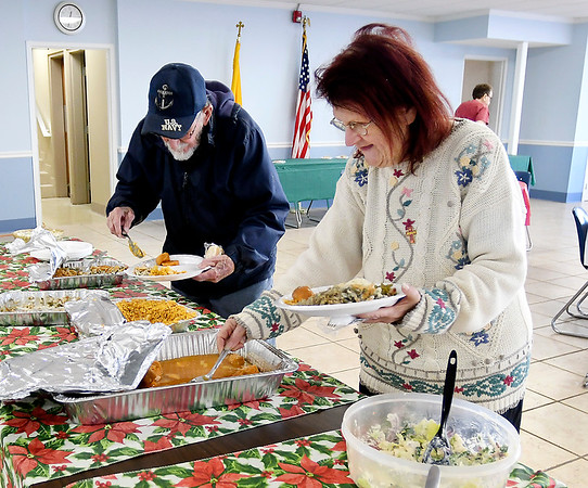 Gene Smith and Linda Jones check out some of the dishes offered Wednesday during the annual Christmas dinner put on by St. Mary's Catholic Church in Alexandria.