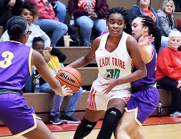 Anderson's Tyra Ford splits the Marion defenders as she drives to the basket.