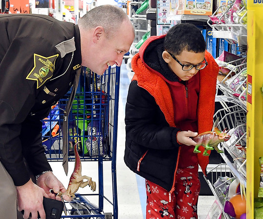 Kyler Hill, 7, tries to decide which dinosaur toy to get as Madison County Sheriffs deputy Mike Warner helps him during their shopping time Tuesday morning at the annual Cops & Kids program at Meijer.